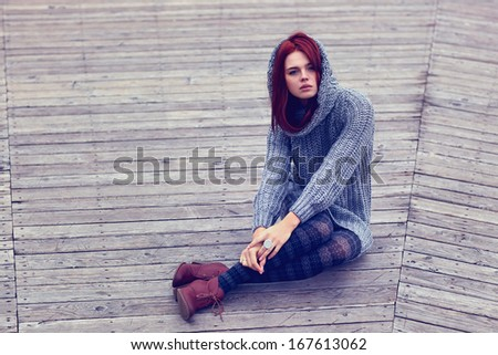 Young slim woman sitting outdoors. - stock photo