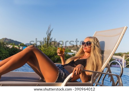 Young slim woman with glass of juice in a sunbed near swimming pool