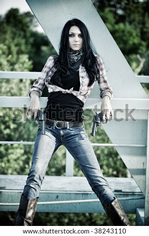 Young slim woman with guns in industrial zone. - stock photo