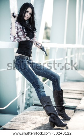 Young slim woman with guns on a bridge. - stock photo