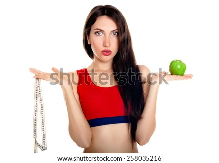 Young slim woman with measuring tape and apple - stock photo