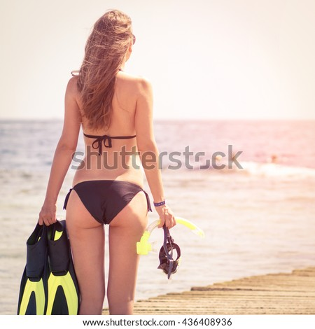 Young slim woman with snorkelling equipment standing near sea. Caucasian girl with flippers, mask and snorkel. Scuba diving or snorkel background - stock photo