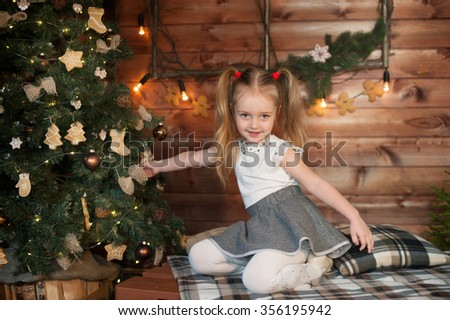 Young sly girl near Christmas tree. New Year celebration. - stock photo