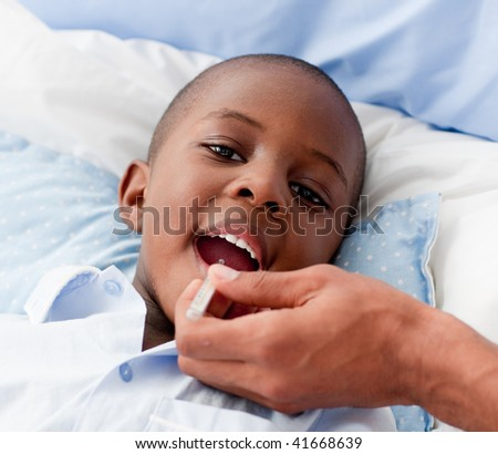 Young Small Boy sick in bed with the flu - stock photo