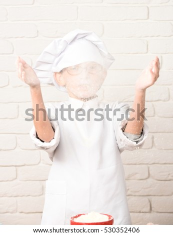 young small cute cook chef in white uniform and hat with glasses playing with flour on brick wall background