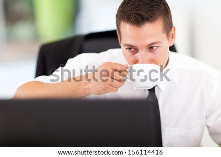young smart business executive having coffee in office while looking at computer screen