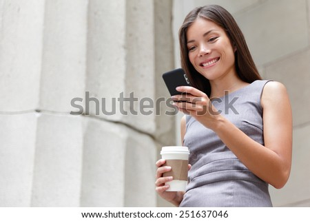 Young smart professional woman reading using phone. Female businesswoman reading news or texting sms on smartphone while drinking coffee on break from work. Mixed race asian caucasian business woman. - stock photo
