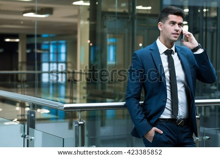 Young, smartly-dressed man talking on the mobile phone inside an office building