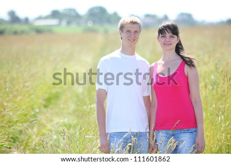 young smile couple hold hands in field near village, wood in day - stock photo