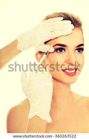 Young smiled woman is having facial botox injection - stock photo