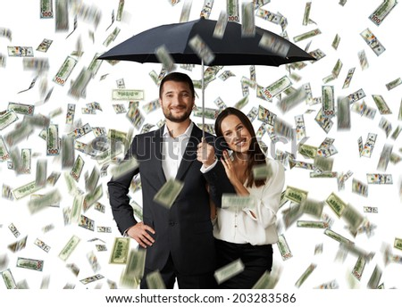 young smiley couple with black umbrella standing under money rain - stock photo