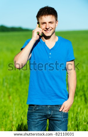young smiley man speaking on his mobile. outdoors - stock photo