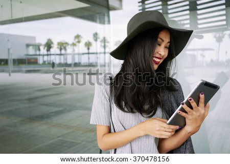 Young smiley well-dressed Asian business woman use digital tablet outside office.  - stock photo