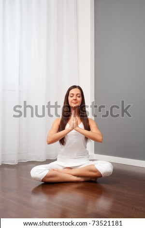young smiley woman doing yoga in room - stock photo