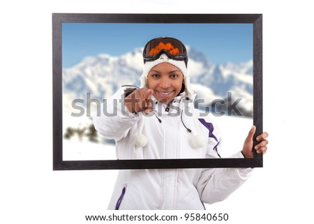 Young smiley woman in ski gears  holding a picture frame, isolated on white background - stock photo