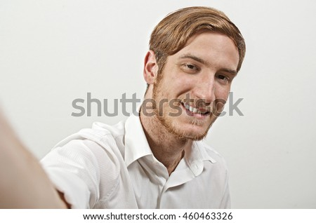 Young Smiling Adult Man in White Shirt Takes a Selfie