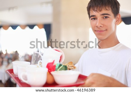 young smiling affable waiter keeps tray with dishes at restaurant - stock photo