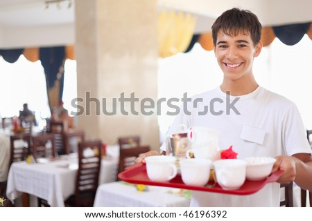 young smiling affable waiter keeps tray with dishes at restaurant, wide angle - stock photo