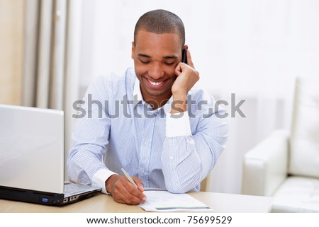 Young smiling african-american businessman calling on phone