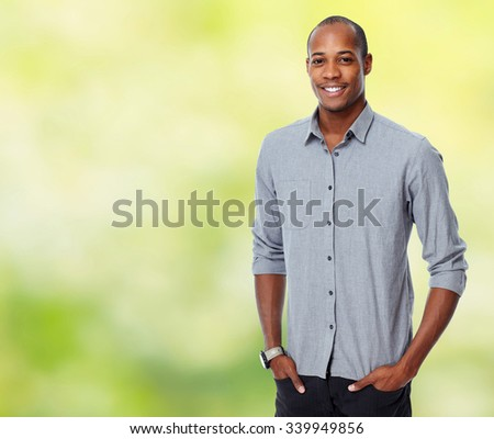 Young smiling African-american businessman over green background.