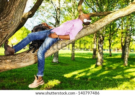 Young smiling african american lying on a tree branch in a park  and listens to music - stock photo