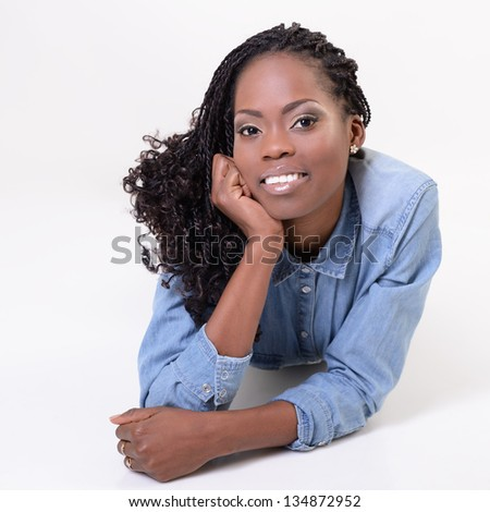 Young smiling african woman posing and looking at camera, over white