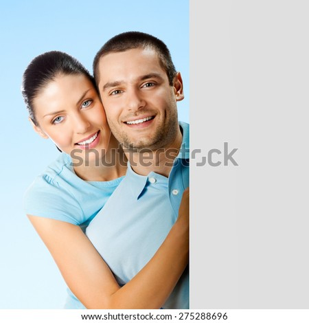 Young smiling amorous attractive couple, against blue sky background, showing blank signboard with copyspace area for text or slogan - stock photo