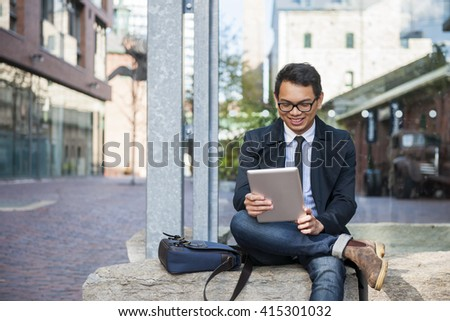 Young smiling asian business man looking at digital tablet sitting outside on city street - stock photo