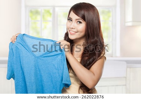 young smiling asian woman showing blue clean clothes - stock photo