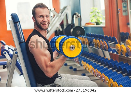 Young smiling athlete lifting weights in the gym - stock photo