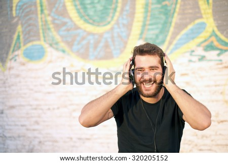 Young smiling attractive man listening to music with earphones - stock photo