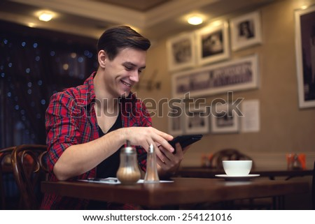 Young smiling attractive man uses his tablet in the lunchtime at the cafe. - stock photo