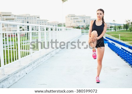 Young smiling attractive sporty girl runner holds her leg while stretching outdoors at stadium of her university campus. Warming up before training. Copy space - stock photo