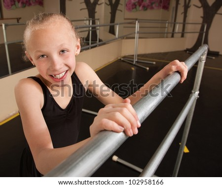 Young smiling ballet student holds railing in dance studio - stock photo