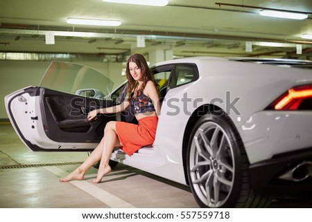 Great Young Smiling Barefoot Woman Sits On Driver Seat Of Modern White Car At  Underground Parking. Amazing Ideas