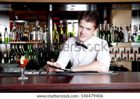 Young smiling bartender taking an order. - stock photo