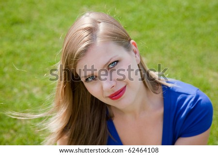 young smiling beautiful blonde girl sitting on the grass in the summer - stock photo
