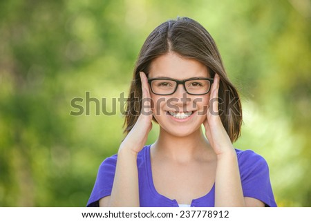 young smiling beautiful girl dark closeups short hair glasses summer park smiling - stock photo