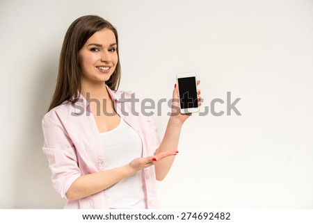 Young smiling beautiful girl showing a blank smart phone screen  on grey background. - stock photo