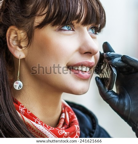 Young smiling beautiful woman in black gloves talking on mobile phone. - stock photo