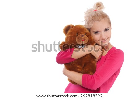 Young smiling beautiful woman in red blouse and jeans holding teddy bear.