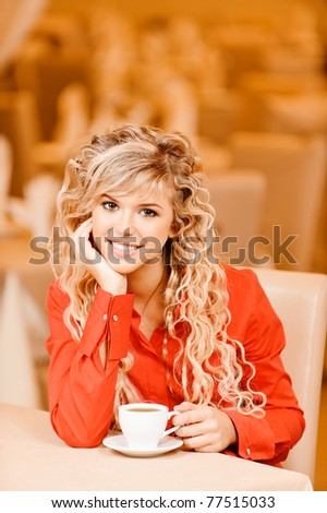 Young smiling beautiful woman in red clothes with curly hair sits at restaurant at little table and drinks tea.