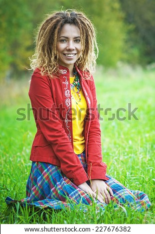 Young smiling beautiful woman with dreadlocks in red clothes sitting in park on grass. - stock photo