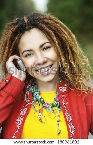 Young smiling beautiful woman with dreadlocks in red dress talking on mobile phone. - stock photo