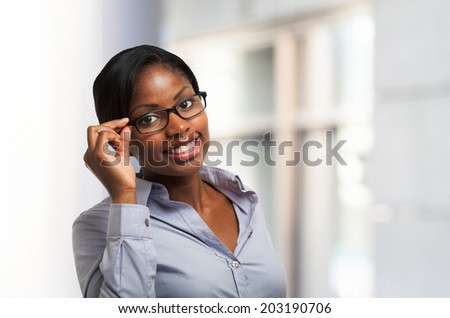 Young smiling black woman holding her eyeglasses - stock photo