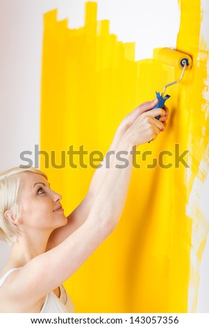 Young smiling blond woman painting the wall yellow with paint roller - stock photo