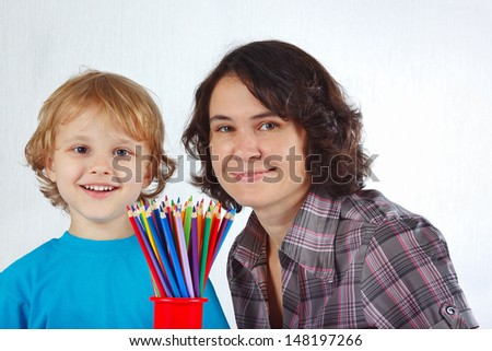 Young smiling boy with his mother with color pencils on a white background - stock photo