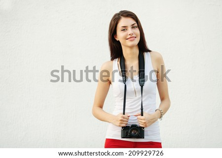 Young smiling brunette woman in white t-shirt posing with a photo camera against a white textured wall - stock photo
