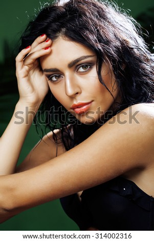 young smiling brunette woman on green background close up - stock photo