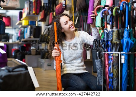 Young smiling brunette woman purchasing automatic umbrella in haberdashery shop - stock photo